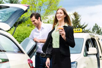 נהג מונית עוזר לנוסעת להעמיס את המזוודה לרכב